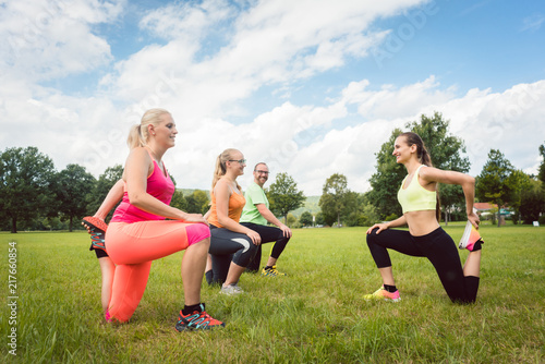 Poster Family with fitness trainer exercising in nature together with sport coach