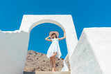 Woman climbing stairs in Greece under a clear blue sky  - 217663263