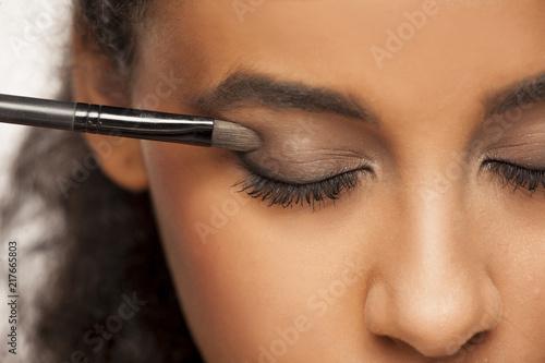 portret młodej kobiety ciemnej karnacji stosując cień do oczu z pędzlem na białym tle