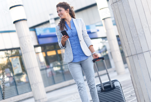 Foto Murales Young woman on business trip walking with her luggage at airport.