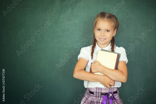 bd922e1ebbcb Child girl with book. Small schoolgirl in uniform clothes holding book  against green blackboard background