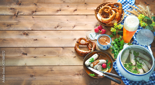Leinwanddruck Bild Bavarian sausages with pretzels, sweet mustard and beer on rustic wooden table