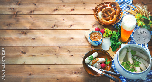 Bavarian sausages with pretzels, sweet mustard and beer on rustic wooden table - 217680299