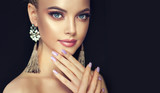 Beautiful model girl with pearl manicure on nails . Fashion makeup and cosmetics . Large earrings tassels jewelry gray color .