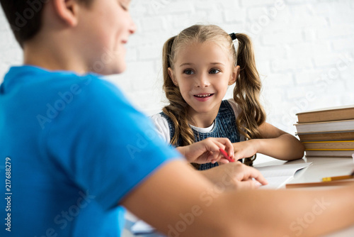 Foto Murales partial view of brother and smiling sister doing homework together at table at home