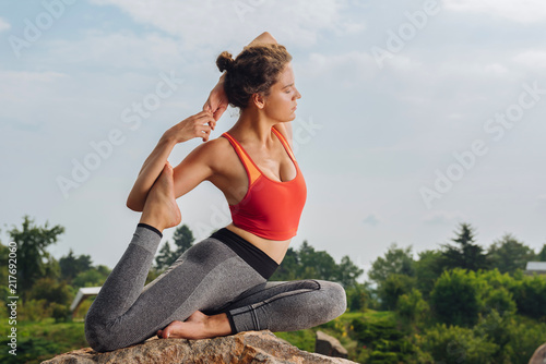 Foto Murales Sitting on rock. Yoga woman wearing comfortable sport clothes practicing asana sitting on rock in the forest