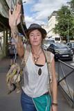 Portrait d'une jeune femme faisant signe d'arrêter en tenant un objet insolite - 217695639