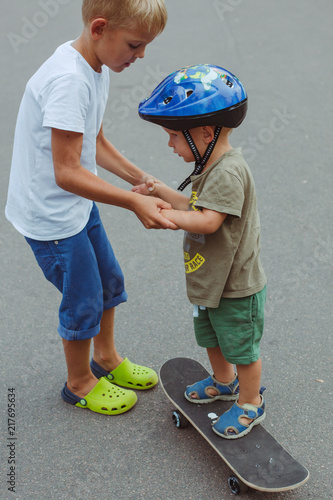 Foto Spatwand Skateboard Two brothers learn to roller skate in summer park