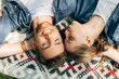 top view of happy young couple with closed eyes lying on patterned cloth