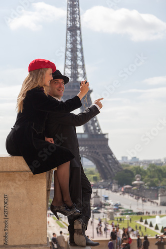Wall mural Happy Couple in Paris Taking Photo with Eiffel Tower Behind Them