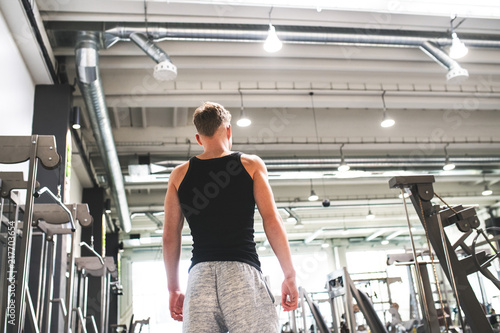 Poster Young man in modern crossfit gym, standing. Rear view.