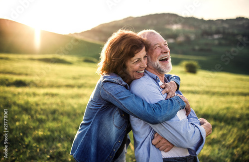 Foto Murales Side view of senior couple hugging outside in spring nature at sunset.