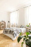 High ceiling bedroom interior with a comfortable bed with leaf pattern linen, a lamp and a bookcase. Real photo. - 217715441