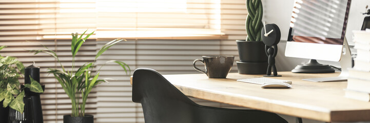Coffee cup, creative clock and a desktop computer on a wooden desk in a sunny workspace interior with plants © Photographee.eu