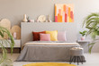 Painting on grey headboard of bed with colorful cushions in bedroom interior with stool. Real photo