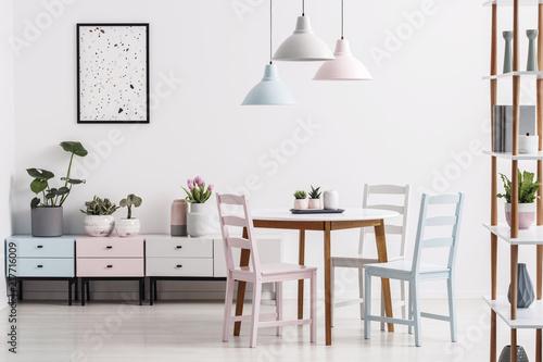 Prawdziwe zdjęcie pastelowego wnętrza jadalni ze stołem, krzesłami, szafkami i plakatem