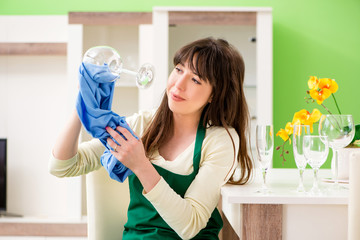 Young woman cleaning glasses at home