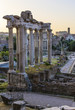 Roman ruins lit by early morning light. There is Colosseum in the background