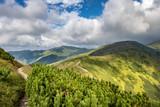 Path through summer mountain ridge under cloudy sky
