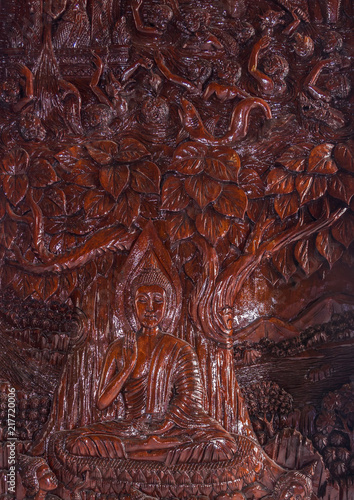 Foto Murales Buddha image carved from a wooden on wall temple in Thailand.