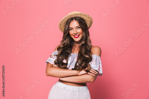 Portrait of adorable glamour woman 20s wearing straw hat smiling and looking at you with arms crossed, isolated over pink background in studio