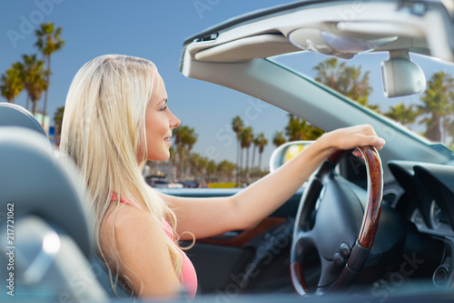 Fridge magnet travel, road trip and people concept - happy young woman driving convertible car over venice beach background in california
