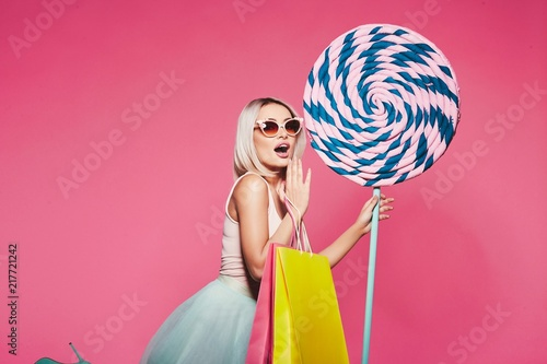 Foto Murales Cute model with sweets and shopping bags
