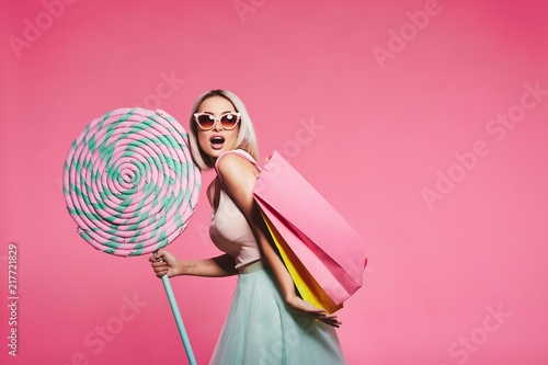 Model posing with with sweets and shopping bags - 217721829