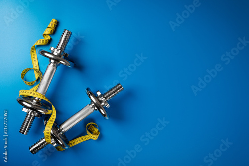 Sticker dumbbells and measuring tape on blue background with copy space