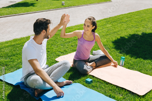 Plakat Great job. Cheerful happy people giving each other high five while sitting on yoga mats