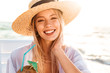 Leinwanddruck Bild - Photo of happy young woman 20s in summer straw hat laughing, and drinking cocktail during sunrise at seaside