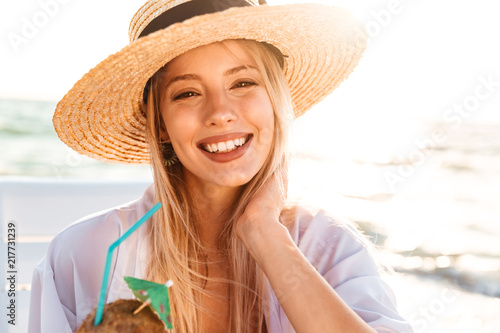 Leinwanddruck Bild Photo of happy young woman 20s in summer straw hat laughing, and drinking cocktail during sunrise at seaside