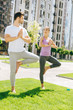 Quadro Yoga partners. Nice young people looking at each other while standing in the yoga pose
