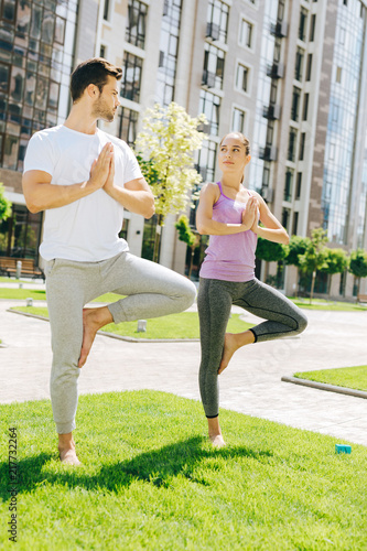 Foto Murales Yoga partners. Nice young people looking at each other while standing in the yoga pose