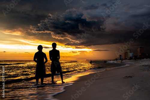 Foto Spatwand Strand Boys watching Beautiful Sunset by the ocean