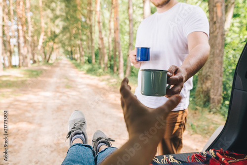Foto Murales man giving metal cup with tea. car hiking concept. copy space