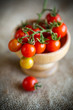 small ripe red cherry tomatoes in a wooden bowl