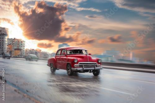 fototapeta na ścianę Schöner Oldtimer fährt am Malecon dem Sonnenuntergang entgegen