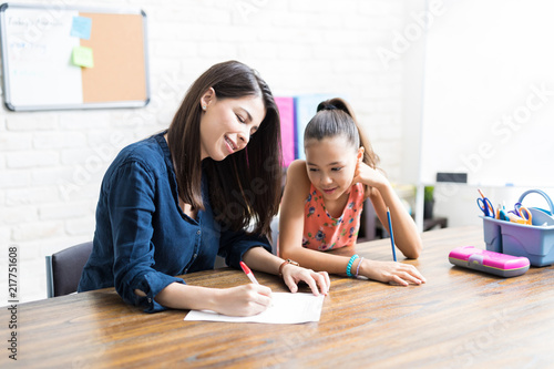 Mother Assisting Daughter With Schoolwork At Table