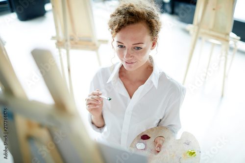 Foto Murales Pensive young woman with paintbrush and palette looking at what she drawing while standing by easel