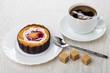 Cake with cream, strawberry jam, sugar,coffee, spoon on table
