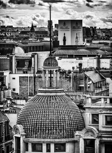 Wall mural Black and white photo of Paris buildings. Beautiful panorama view from famous Printemps store in France. Panoramic view from rooftop.