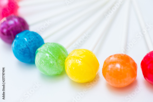 Foto Murales Rainbow design of sweet colorful lollipops against white background