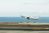 departure of white jet airplane, runway and blue sea background