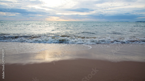Foto Murales Sand beach with sea waves in the sunset.
