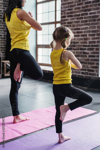 Leinwanddruck Bild Mother and daughter practicing yoga together meditating standing on one leg with hands in prayer