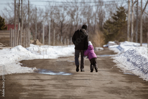 Foto Murales Girl with dad walking on the road in winter