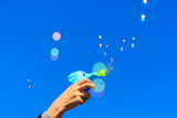 Hand with soap bubbles against the blue sky