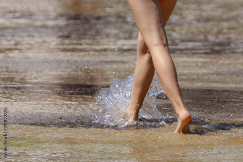 Foto Murales The legs of a girl in the water in a fountain
