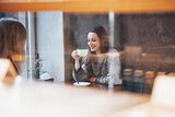 Two friends enjoying coffee together in a coffee shop as they sit at a table chatting - 217824251